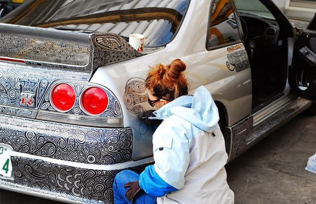 Девушка разрисовывает автомобиль