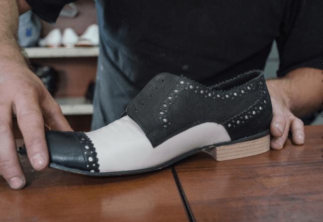 Отремонтированный черно-белый ботинок в мужских руках
