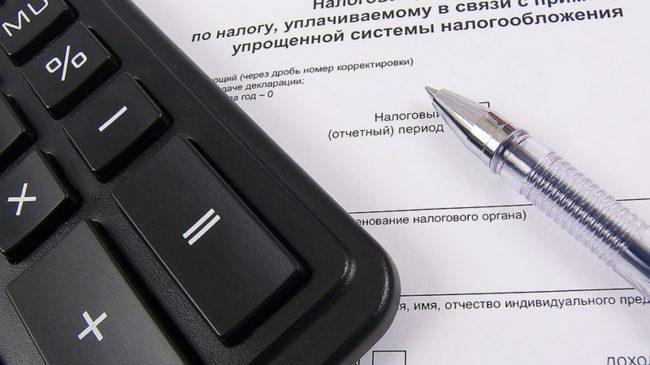 Калькулятор и ручка на фоне документа
