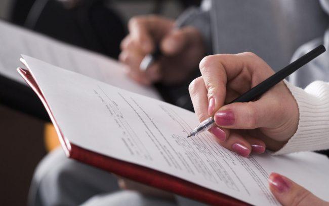Крупным планом рука женщины при заполнении документа