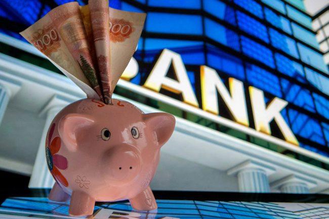 Пятитысячная купюра в свинье-копилке на фоне банка