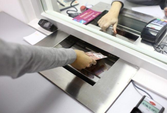 Девушка отдает деньги кассиру банка