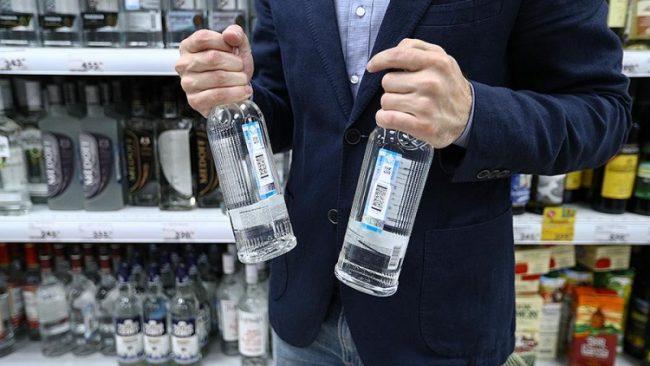 Мужчина держит две бутылки водки