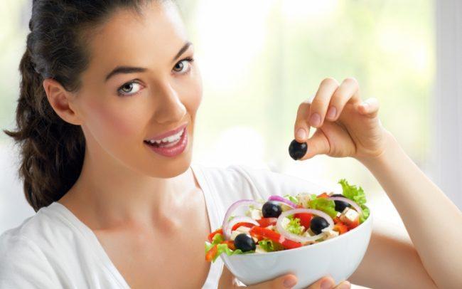 Девушка держит миску с салатом
