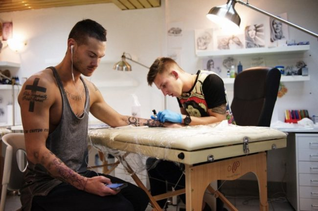 мужчина делает татуировку