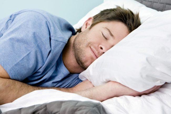 Мужчина спит на кровати