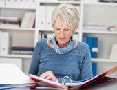 Женщина сидит за столом с документами