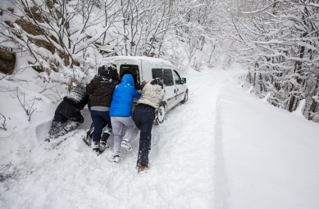 Мужчины выталкиват автомобиль из сугроба