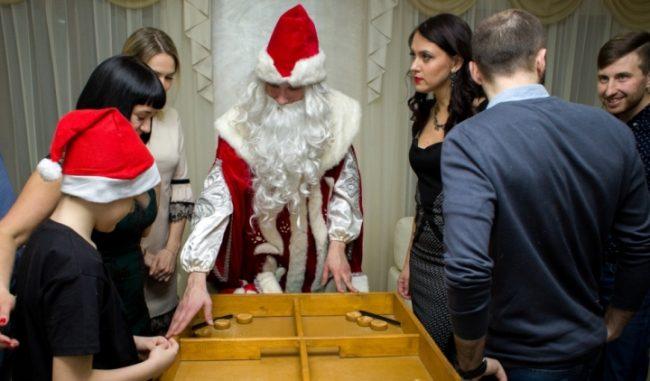 Дед Мороз и семья, играющие в настольную игру