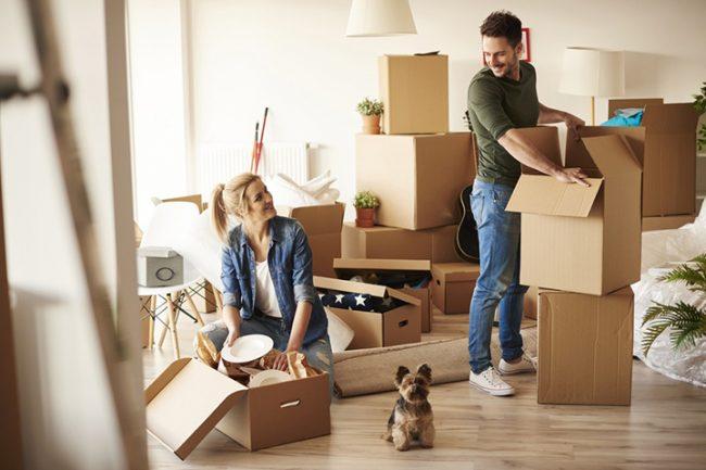 Молодая пара распаковывает вещи в новой квартире
