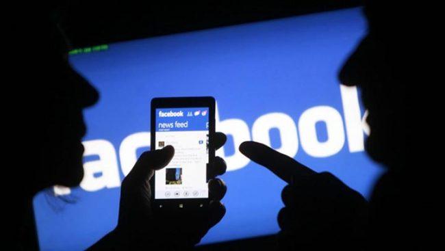 Два человека смотрят на смартфон с открытым приложением Facebook