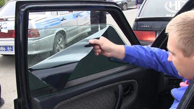 Мужчина сдирает тонировку со стекла