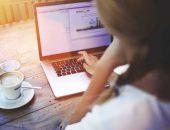 Девушка работает на ноутбуке с чашечкой кофе
