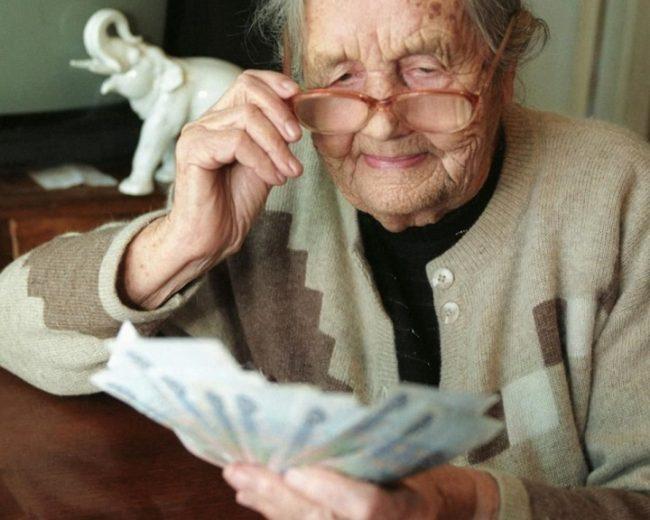 Бабушка держит в руках деньги