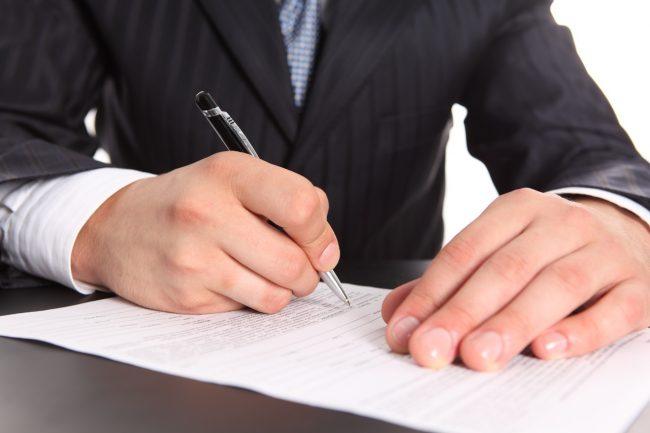 Крупный план мужских рук с шариковой ручкой и документом