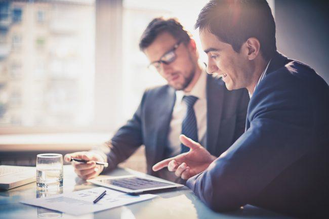Двое мужчин в деловых костюмах во время беседы