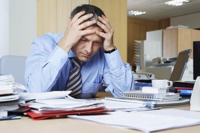 Мужчина, сидя за рабочим столом, держится за голову