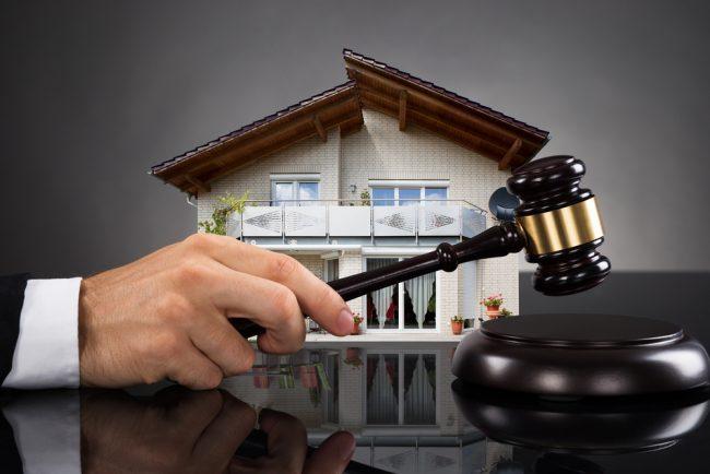 Судейский молоток в руках и дом