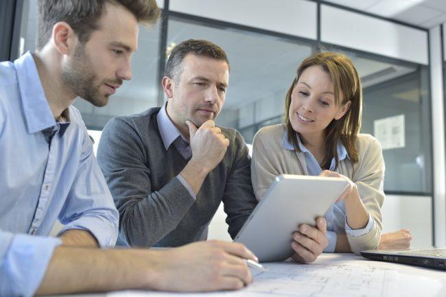 Три человека смотрят в планшет