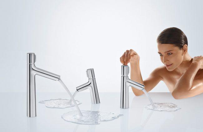 Девушка смотрит на краны с текущей водой