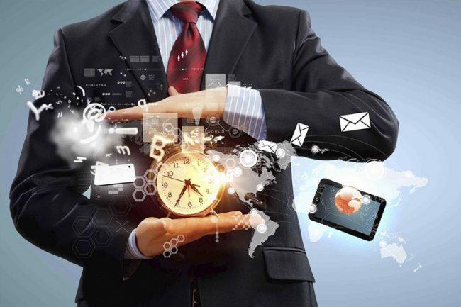 Мужчина в деловом костюме держит в руках часы и совершает виртуальные действия с письмами, отчётами и пр