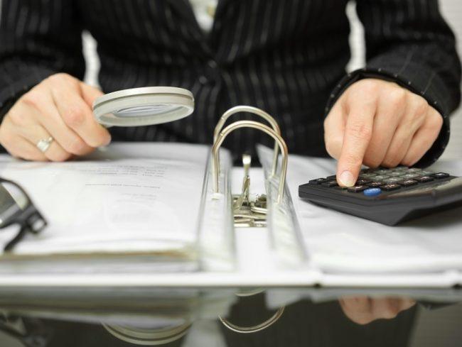Человек с лупой и калькулятором сидит за столом над бумагами