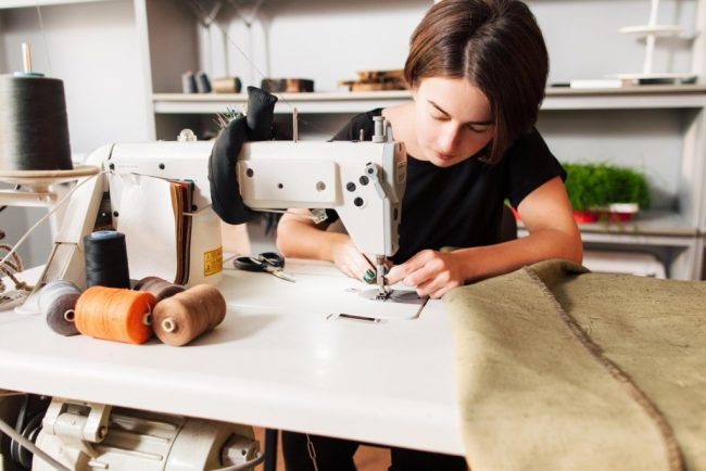Женщина за швейной машинкой работает с кожей