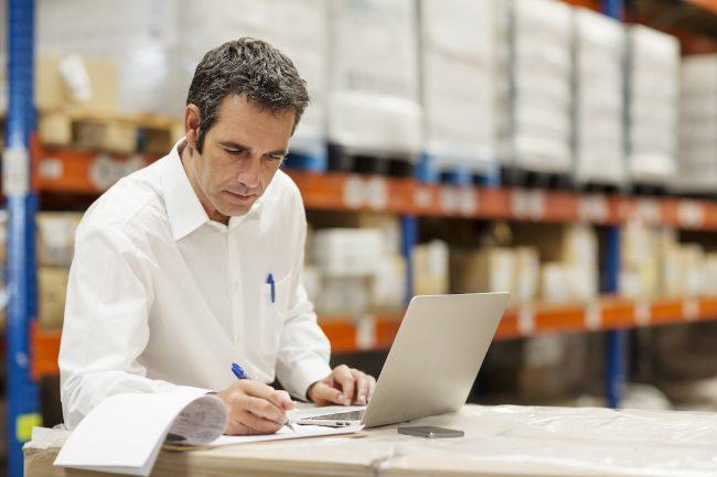 Мужчина на складе с ноутбуком и бумагами