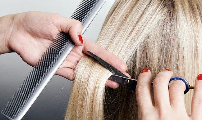 Парикмахер стрижёт волосы