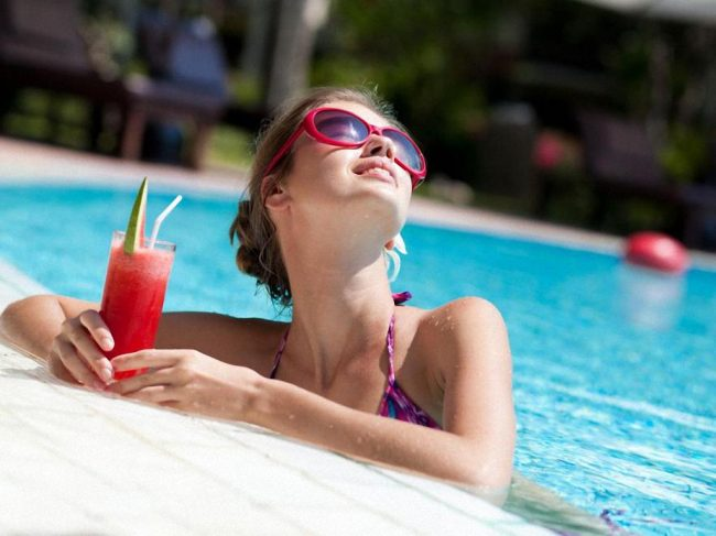 Девушка в бассейне со стаканом сока
