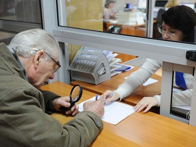 Пожилой россиянин получает пенсию в кассе