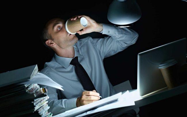 Работающий мужчина пьёт кофе