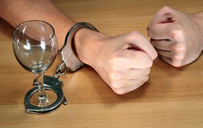 Рука пристёгнута наручниками к бокалу