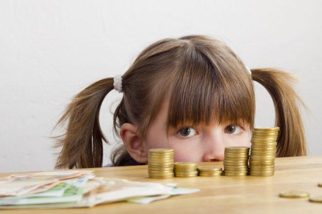 Девочка за столом с деньгами