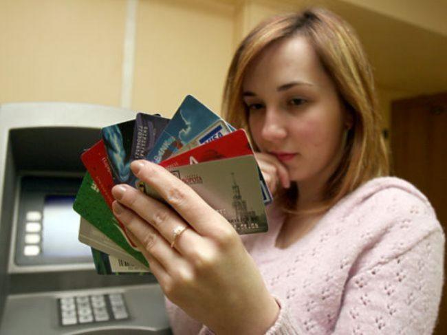 У девушки несколько пластиковых карт в руках