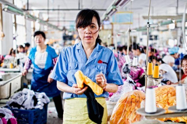 Женщина работает в китайском цехе по производству одежды