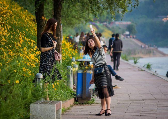 Китаянки гуляют и фотографируются в парке