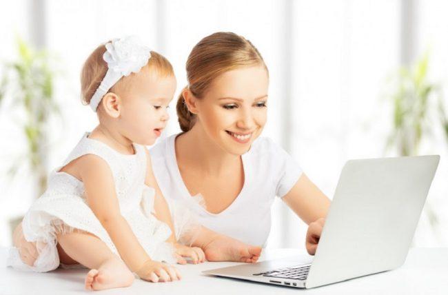 Молодая мама работает с ноутбуком