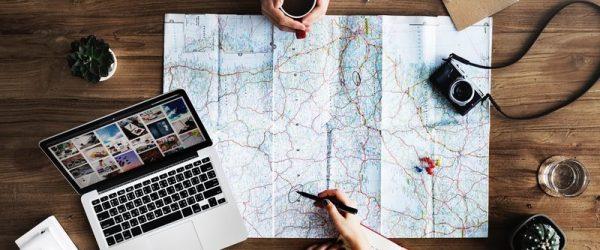 Парень с девушкой отмечают маршрут путешествия на карте