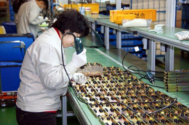 Женщина работает в производственном цехе