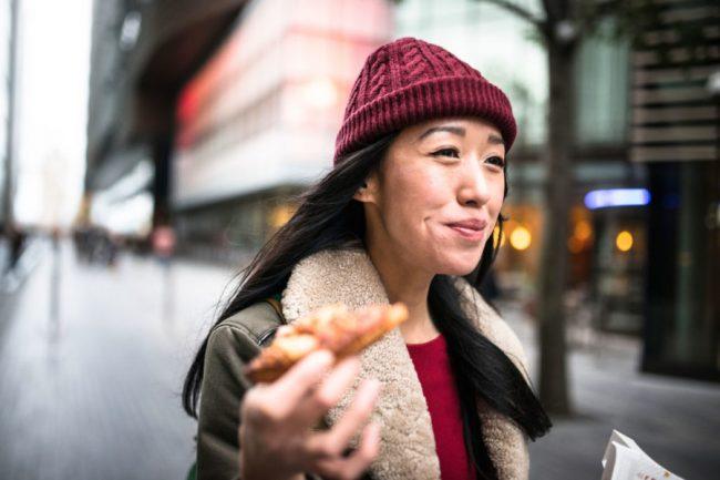 Девушка ест на ходу на улице