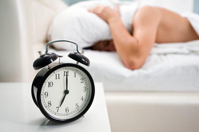 Часы с будильником на прикроватной тумбочке