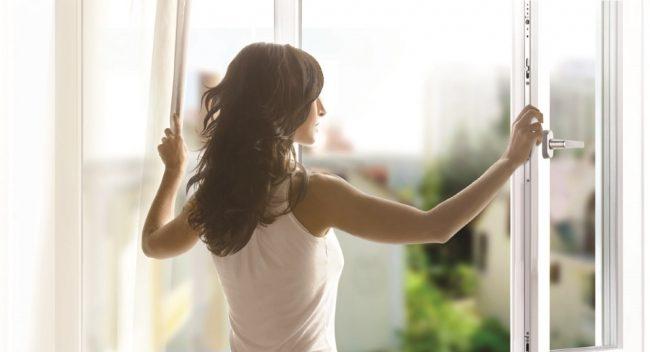 Девушка стоит у открытого окна