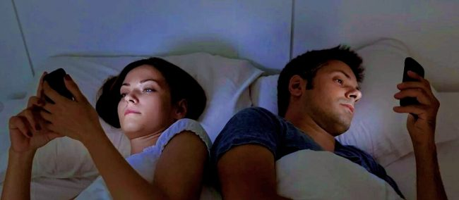 Парень и девушка лежат на кровати и смотрят в смартфоны
