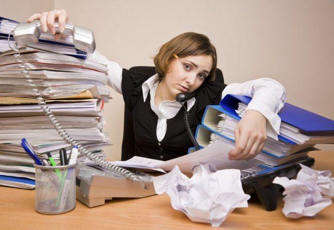 Девушка сидит за столом, заваленным папками с бумагами