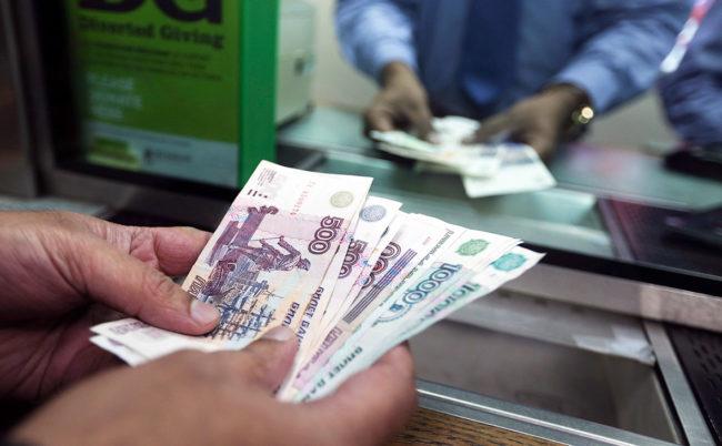 Мужчина с деньгами в банковской кассе