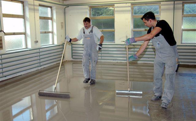 Два работника делают наливной пол